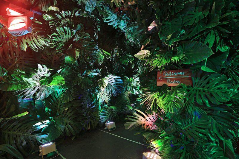 Rotulo de baños sobre pared decorada de hojas tropicales